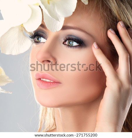 Beautiful Girl With White Orchid Flowers. Beauty Model Woman Face. Perfect Skin. Professional Make-up. Makeup. Fashion Art - stock photo