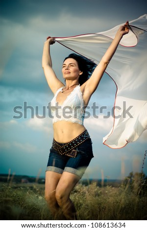 Beautiful girl with white scarf jumping  in a summer field - stock photo