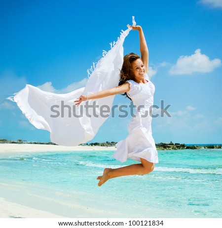 Beautiful Girl With White Scarf Jumping on The Beach. Travel and Vacation. Freedom Concept - stock photo