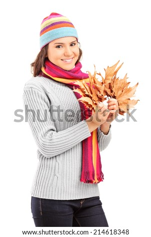 Beautiful girl with winter hat holding dry leaves isolated on white background - stock photo