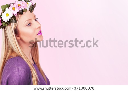 Beautiful girl with wreath of flowers in her hair. Young pretty blue eyes girl with flowers in a hair, isolated on pink background. Head and shoulders. Profile. Studio shoot. - stock photo