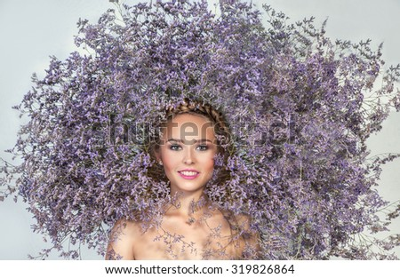 Beautiful Girl With wreath of  Purple Flowers. Beauty Model Woman Face. Perfect Skin. Professional Make-up.Makeup. White background. - stock photo