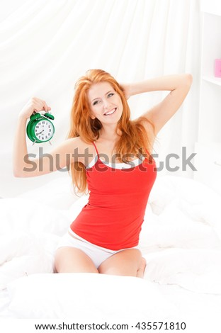 Beautiful girl woke up and sitting on a bed in the early morning. Beautiful young woman in underwear holding alarm-clock in the bedroom. - stock photo