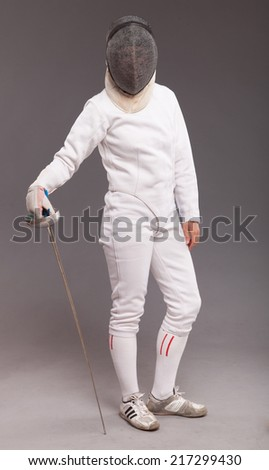 beautiful girl woman with sword in fencing costume and fencing mask