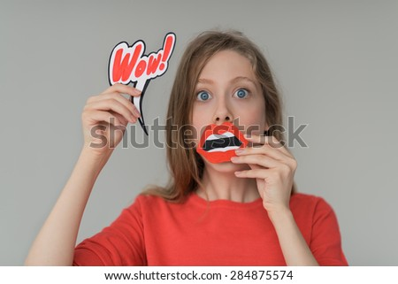 Beautiful girl wondering and surprised portrait - holding fake paper mouth and wow sign - stock photo