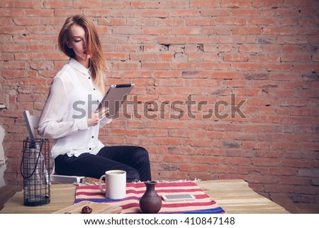 Beautiful girl working behind the plate at the table . Brick background