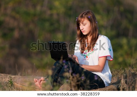 Beautiful girl working on computer outdoor in nature