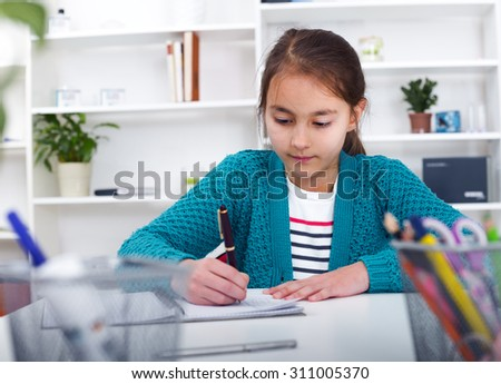 Beautiful girl working on her school project at home - stock photo