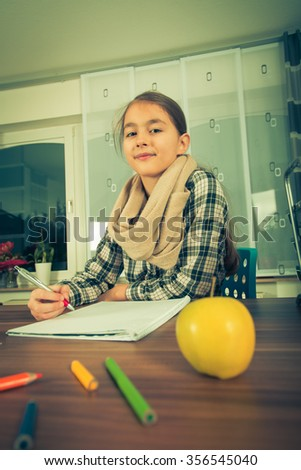 Beautiful  girl working on her school project at home.Vintage photo - stock photo