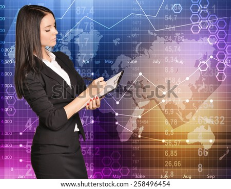 Beautiful girl writes a pen holder paper. standing on a colorful of the financial background - stock photo
