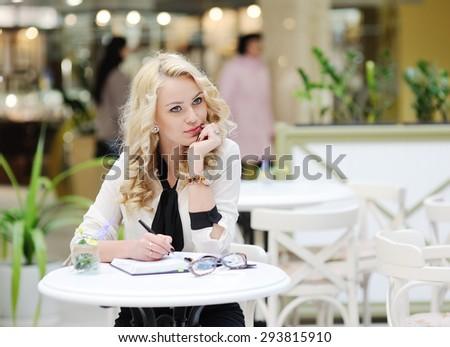 beautiful girl writing in a notebook - stock photo
