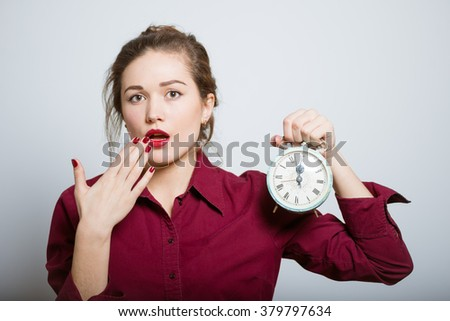 Beautiful girl yawning with an alarm clock, isolated on a gray background