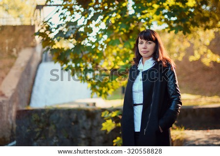 beautiful girl 30 years in business suit walking in the autumn forest - stock photo