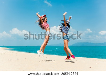 beautiful girlfriend jump in shorts and caps on the beach near the sea and rejoice