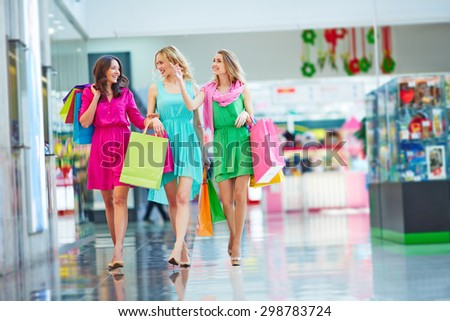 Beautiful girlfriends with paperbags shopping together - stock photo