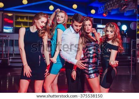 Beautiful girls and man having fun at a party in nightclub - stock photo
