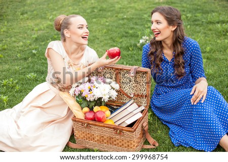 Beautiful girls are making picnic in the nature. They are sitting on grass near a basket of food. The girl is proposing an apple to her friend. They are laughing - stock photo