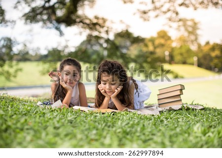 Beautiful Girls are Reading chrildren Bible. lying in park - stock photo