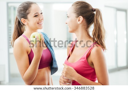Beautiful girls at the gym enjoying and talking together during a workout break, one is holding an apple, fitness and healthy lifestyle concept - stock photo
