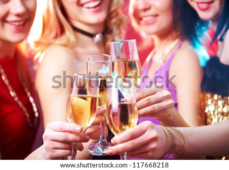 Beautiful girls clink glasses of champagne at a party. unrecognizable people - stock photo