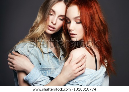 Beautiful Girls Couple. Hug of two Women. Blonde and red Hair Models