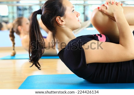 Beautiful girls doing situp workout training in the gym - stock photo
