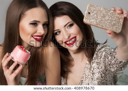 Beautiful girls eating cakes and making a photo of themselves. Red lips.  Smiling ladies. Fashion Brunette and blonde Portrait on a silver background. Gorgeous Woman Face. Ladies on the party.   - stock photo
