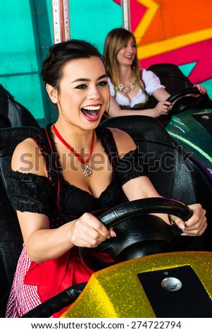 Beautiful girls in an electric bumper car in amusement park in typical German Dirndl dresses with bright colours and lights in the background - stock photo