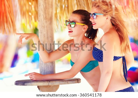 beautiful girls in bikini talking on tropical beach, summer vacation - stock photo