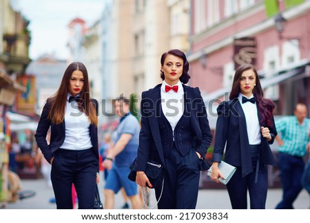 beautiful girls in black suits walking the street - stock photo