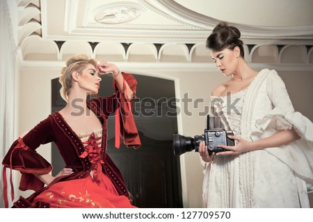 Beautiful girls in palace are making photos - baroque style - stock photo