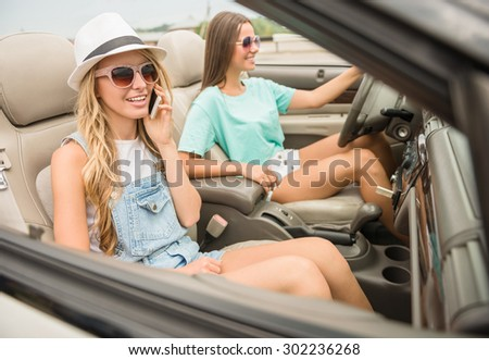 Beautiful girls in sunglasses driving on cabriolet. Blonde talking by phone. - stock photo
