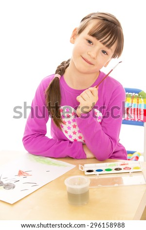 Beautiful girls Schoolgirls with short bangs on her head holding a brush to paint with watercolors , girl sits at a table in front of her a sheet of paper - isolated on white background - stock photo