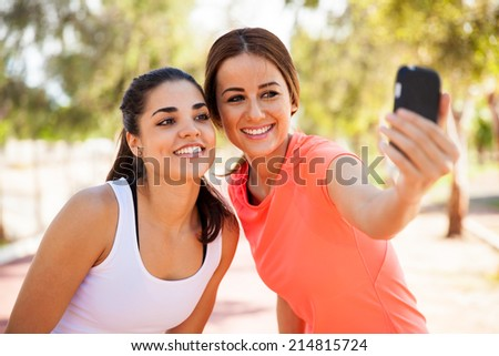 Beautiful girls taking a selfie with a smart phone before going for a run outdoors - stock photo