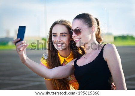 "Beautiful girls taking a ""selfie"" with their cell phone - stock photo"