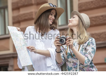 Beautiful girls tourists are looking for an address on the map on a city street. They are wearing hats and smiling. Outdoors. Summer day.
