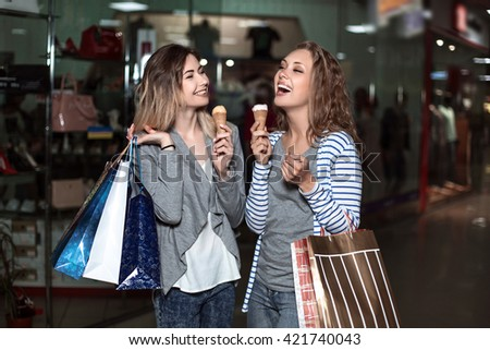 Beautiful girls with eating ice cream. Fashion Shopping two ladies Portrait. Beauty Woman with Shopping Bags in Shopping Mall. Shopper. The concept of good mood and fun. Shopping Center
