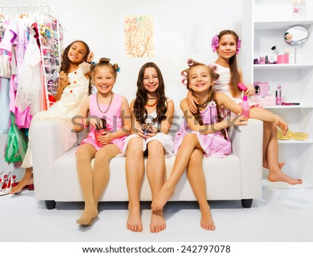 Beautiful girls with hair-curler sit on white sofa - stock photo