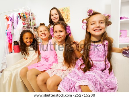 Beautiful girls with hair-curlers sitting on white sofa of beauty salon together - stock photo