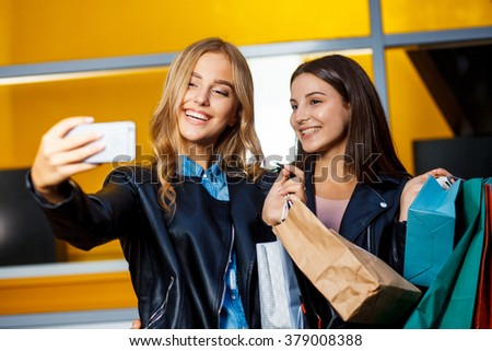 beautiful girls with shopping bags in ctiy. Taking selfie. - stock photo