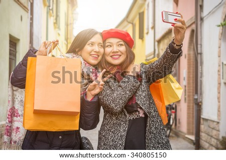 """Beautiful girls with shopping bags taking a """"selfie"""" with their cell phone - caucasian and asian people - technology and lifestyle concept - stock photo"""