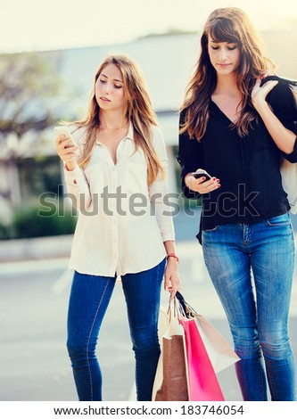 Beautiful girls with shopping bags using their cell phones - stock photo