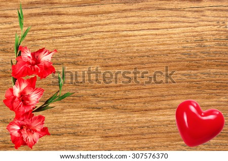 Beautiful gladiolus and red heart on wooden background - stock photo