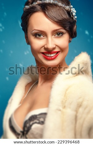 Beautiful glamor girl in a white fur coat with red lips and a beautiful decollete - stock photo