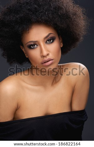 Beautiful glamorous Afro-American woman with a frizzy afro hairdo and bare shoulders - stock photo