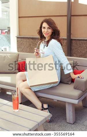 Beautiful glamorous girl in a dress with a paper sack rest after shopping. Luxury girl in a checkered dress with sunglasses.  - stock photo