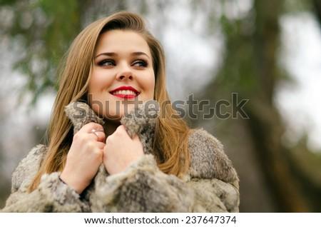 Beautiful glamorous lady having fun outdoor on gloomy winter day. - stock photo