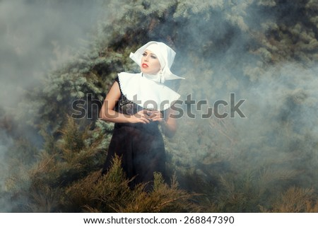 Beautiful glamorous nun looks up amid the smoke, in the background nature. - stock photo