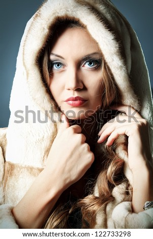 Beautiful glamorous woman in fur coat posing at studio.
