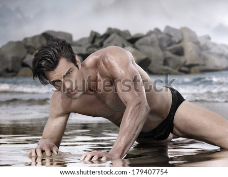 Beautiful glamour male model on moody exotic beach - stock photo